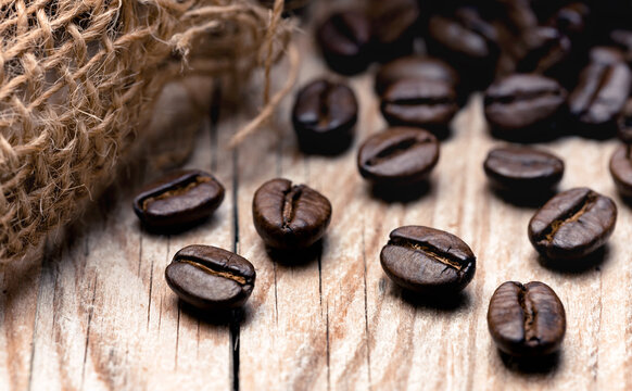 Roasted coffee beans on a wooden surface (close-up)