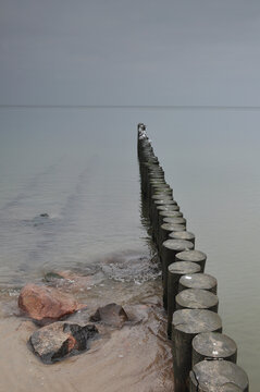 Wooden breakwater on Baltic sea in cloudy weather in evening