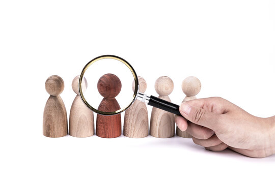 Vertical shot of a hand holding a magnifying glass on wooden figures  isolated on white background