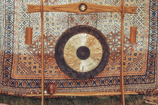 Traditional oriental gong on a beautiful ornamental background.