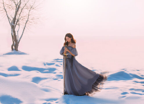 Fantasy woman princess warrior holding medieval iron sword in hands. Fairy tale snow queen. vintage gray blue dress. White winter nature background, valley, tree. Elf girl with steel blade. Art photo.