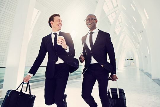 Two smiling businessmen running down an airport departure hall