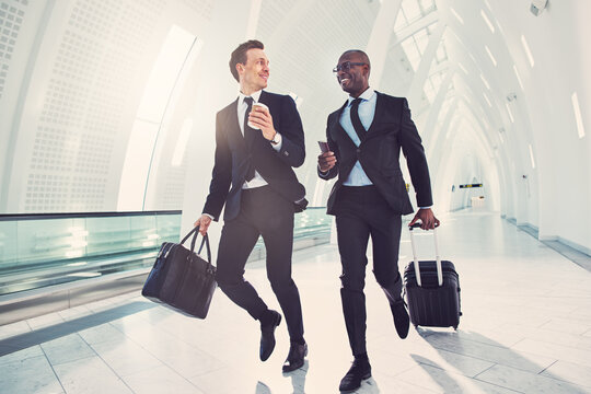 Two smiling businessmen rushing through an airport for a flight