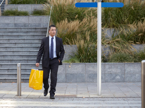 businessman walking with shopping bag
