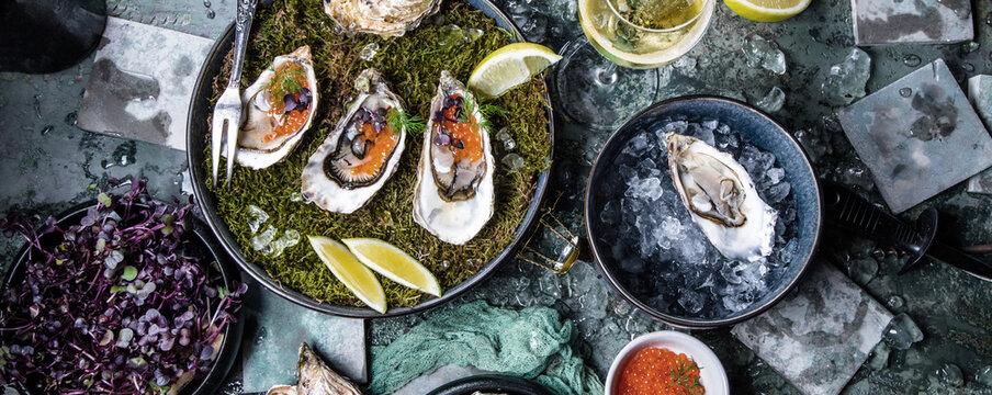 Leckere Austern auf Eis mit Zitrone. Raffiniert mit Kräutern und Lachskaviar.