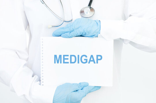 Doctor holds a card with the name of the diagnosis MEDIGAP. Medical concept.