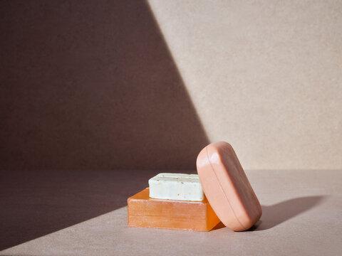 empilement de savons artisanaux pour le corps ou les mains, soins d'hygiène écologiques sur un fond neutre baigné de soleil