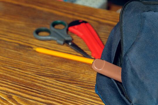 POD e-cigarette or nicotine vapor stick a by school bag.