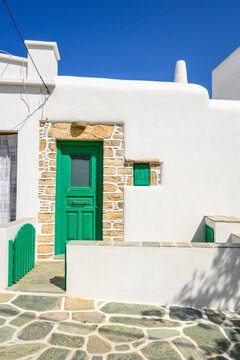 Building with green doors on whitewashed street in beautiful Chora town on Folegandros Island, Cyclades, Greece.