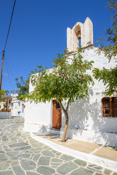 Small square with church building on whitewashed street in beautiful Chora town on Folegandros Island, Cyclades, Greece.