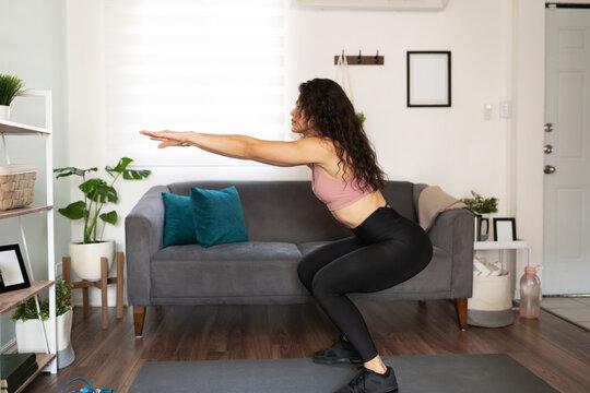 Hispanic woman practicing squat exercises at home