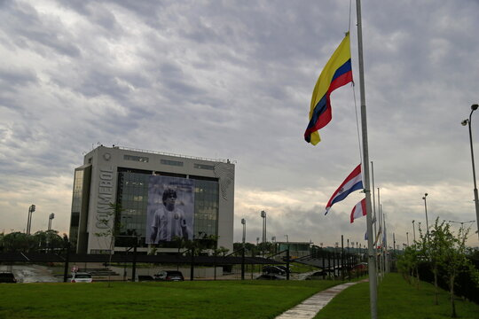 A picture of soccer legend Diego Maradona hangs in the front of the CONMEBOL headquarters as flags fly at half-mast following the death of Maradona, in Luque