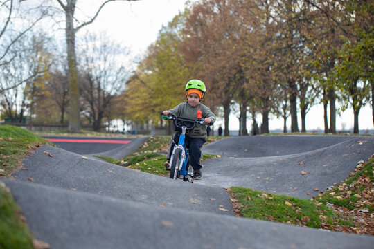 Handsome little boy driving bicycle on a track