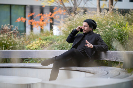 Handsome young man talking on the phone outside