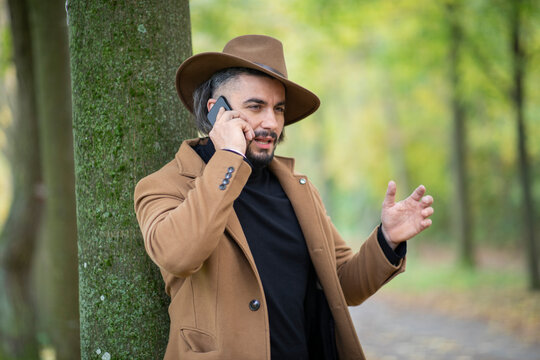 Handsome young man with cowboy hat talking on the phone