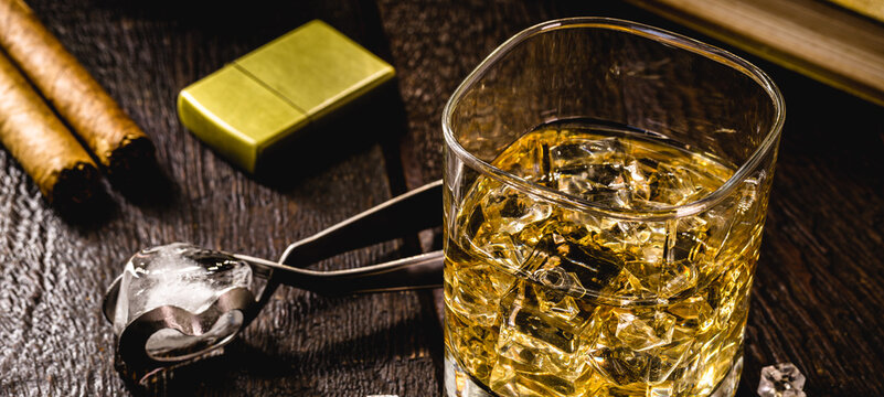 glass with whiskey and ice tongs in the background. Bar or pub image. Relaxation concept, luxurious lifestyle