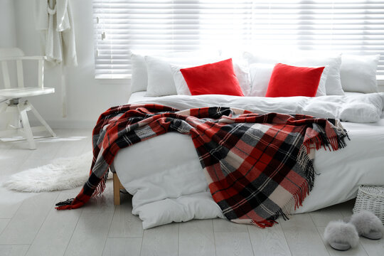 Comfortable bed with warm checkered plaid in stylish room interior