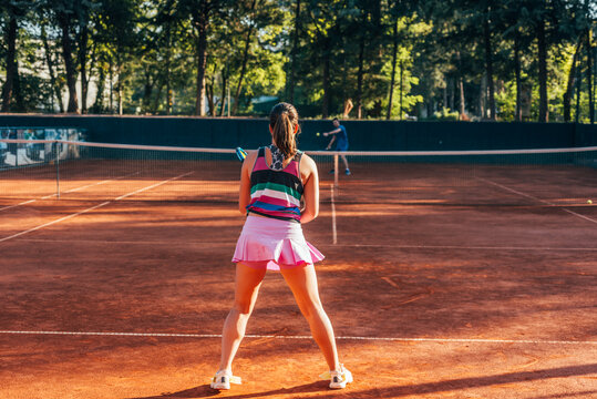 View from the back of a young female paying tennis on a court outside
