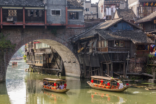 FENGHUANG, CHINA - AUGUST 14, 2018: Boats passing under the arch of Hong bridge in Fenghuang Ancient Town, Hunan province, China