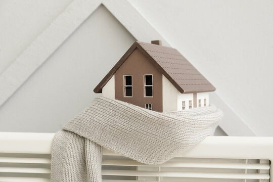 Figure of house and scarf on radiator. Concept of heating season