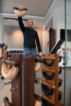 A man tries out weights made from leather in a showroom of U.S. gym equipment manufacturer WaterRower in Munich