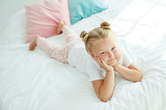 Nice baby girl enjoys a sunny morning. Good morning at home. The girl wakes up from sleep. High quality photo.
