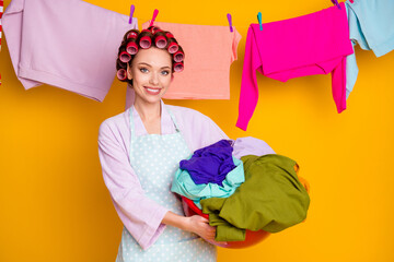 Portrait of attractive hardworking cheerful maid holding in hand dirty wear things isolated bright...