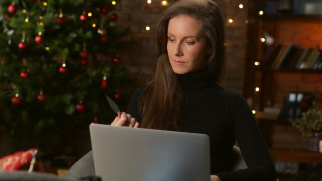 Woman shopping for Christmas gifts online from home in decorated living room with laptop and credit card.