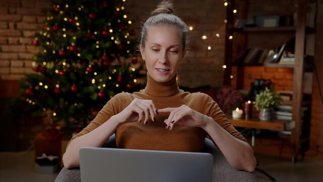 Young woman at home in Christmas time talking on video chat online on laptop computer. Happy and smiling, christmas tree in background.