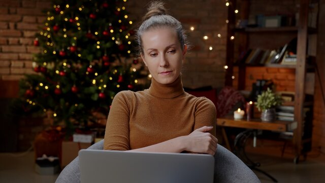 Woman working on laptop computer at home in winter at Christmas in December, Winter.