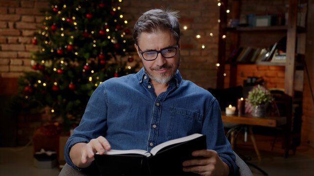 Mid-adult older in glasses man reading book at home at Christmas in winter, dark room with Christmas tree.