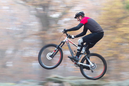 Man cycling fast with mountainbike in a forest in fall