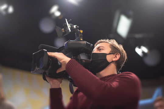 masked cameraman is filming a television show in the studio.