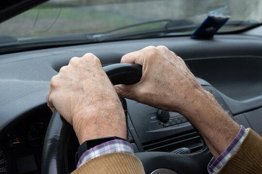 Old man's hands on car steering wheel