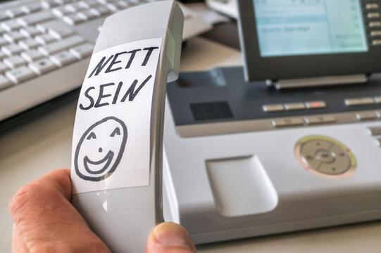 """Vermerk """"Nett sein"""" in deutscher Sprache auf dem Hörer eines Telefones zur Erinnerung an freundlichen Umgang mit dem Anrufer"""