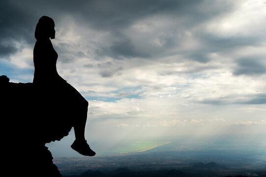 Frau auf einem Felsen mit weitem Ausblick Richtung Meer mit Textfreiraum im Himmel