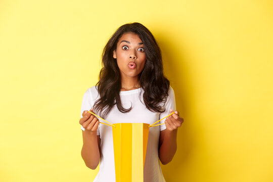 Image of surprised african-american girl receive a gift on holiday, open a shopping bag and looking amazed, standing over yellow background