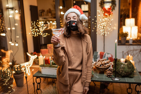 Young happy woman in facial mask celebrating alone New Year holidays at home. Concept of quarantine and self-isolation during the epidemic on holidays