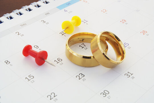 Planning wedding concept. Golden wedding rings with push pins on calendar background.