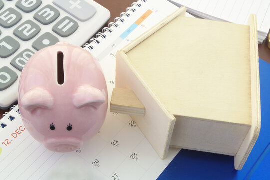 Wooden house and piggy bank on calendar with calculator, Real estate business concept.