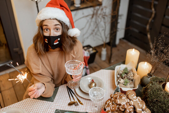 Young woman in facial mask celebrating alone New Year holidays at home. Concept of quarantine and self-isolation during the epidemic on holidays