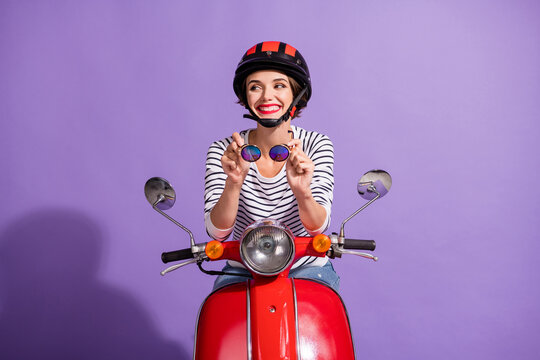 Portrait photo of curious happy girl in helmet on motorbike smiling looking at blank space isolated on vibrant violet background