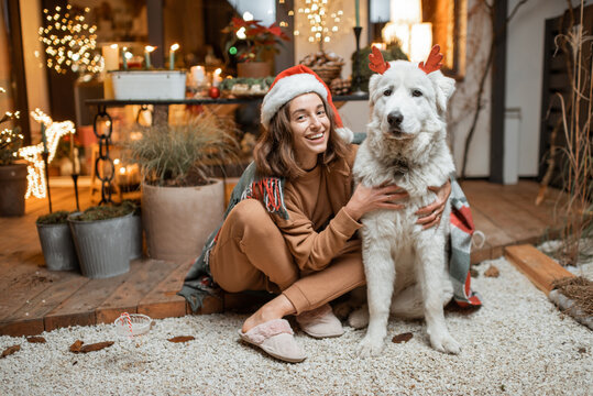 Portrait of a woman in christmas hat with her cute dog celebrating a New Year holidays, sitting together on the beautifully decorated terrace at home