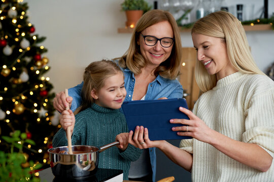 Three generations of women using a tablet in the kitchen
