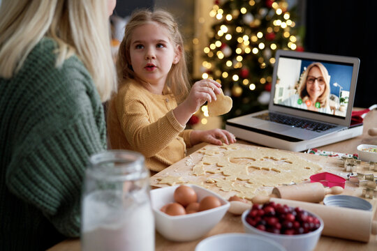 Surprised little girl with Christmas cookies looking at mother