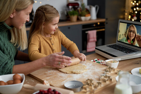 Mother and daughter baking during video conference with grandma