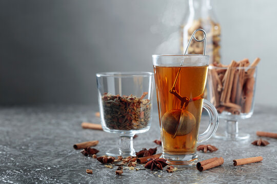 Herbal tea with spices on a grey background.