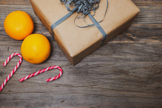 Saint Nicholas concept with brown gift box, oranges and striped candy canes on wooden background.