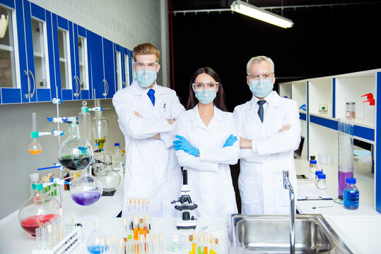 Group of three assistants doing vaccine experiment in lab all wearing labcoats gloves glasses gauze masks folded arms