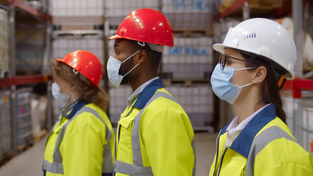 Side view diverse team of industrial workers in helmet and safety mask walking in large warehouse